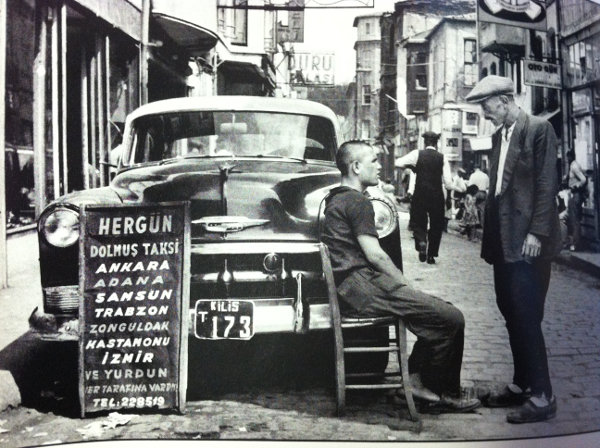 (old picture of 2 men and a taxi in the street)